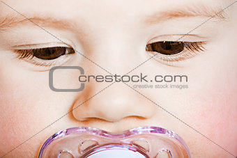 face baby with pacifier closeup. macro