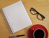 Overhead of notebook and glasses with pen and coffee cup