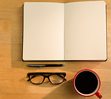 Overhead of open notebook with pen glasses and coffee