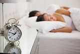 Couple lying in bed with focus on alarm clock