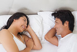 Happy couple lying in bed chatting