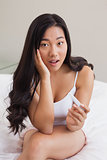 Shocked woman sitting on bed holding pregnancy test