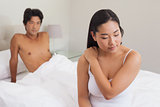 Boyfriend looking at girlfriend sitting on end of bed