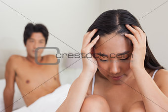 Boyfriend looking at upset girlfriend sitting on end of bed