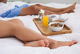 Couple lying on bed with breakfast on a tray