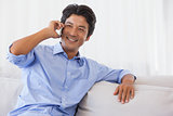 Happy man sitting on couch on the phone