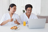 Happy couple using laptop over breakfast