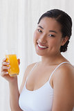 Pretty asian woman holding glass of orange juice