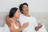 Smiling asian couple lying on bed watching tv