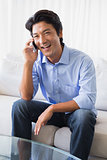 Happy man sitting on couch talking on phone