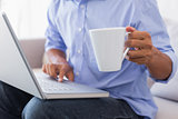 Man sitting on couch using laptop having coffee
