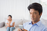 Man sending a text while girlfriend watches from couch