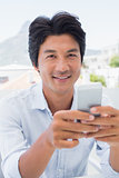 Happy man texting on phone