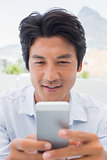 Smiling man sending a text message