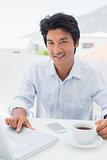 Smiling man having coffee and using laptop