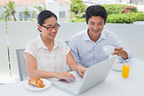 Smiling couple having breakfast together using laptop