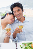 Happy couple having white wine with a meal