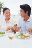 Happy couple having a meal together with white wine