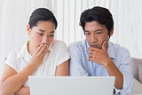 Worried couple using laptop together