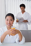 Woman in bathrobe having orange juice with boyfriend in background