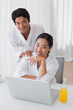 Couple in bathrobes using laptop together in the morning