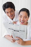 Couple in bathrobes reading newspaper together in the morning