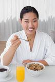 Happy woman in bathrobe having her breakfast