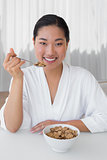 Happy woman in bathrobe having her breakfast