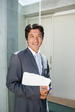 Confident estate agent standing at front door with clipboard