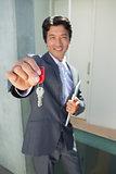 Confident estate agent standing at front door showing key
