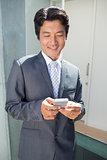 Confident estate agent standing at front door texting