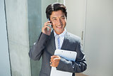 Confident estate agent standing at front door on the phone