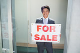 Confident estate agent standing at front door showing for sale sign