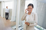 Estate agent talking on phone with buyer in background