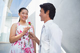 Man offering a red rose to girlfriend