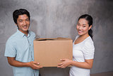 Happy couple holding a cardboard moving box