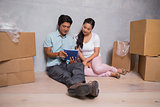 Happy couple sitting on floor using tablet surrounded by boxes