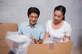 Happy couple sitting on floor unpacking boxes