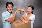 Happy couple holding house key and leaning on moving box