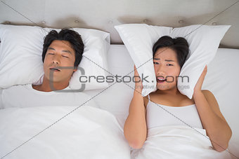 Annoyed woman covering her ears with pillows to block out snoring