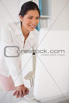 Casual businesswoman smiling at computer