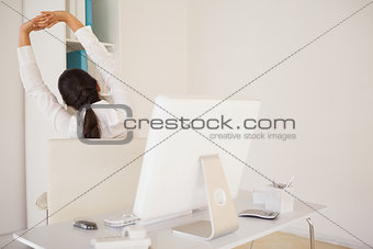Casual businesswoman stretching at her desk