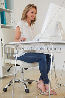 Casual businesswoman sitting at her desk