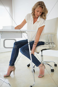 Casual businesswoman touching her ankle