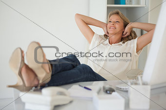 Casual businesswoman sitting at her desk with feet up