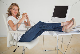 Casual businesswoman having a coffee with her feet up at desk