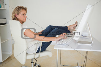 Casual businesswoman working with her feet up at desk