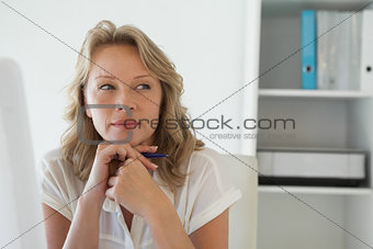 Casual businesswoman thinking at her desk