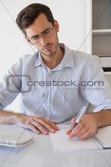 Casual businessman taking notes at his desk