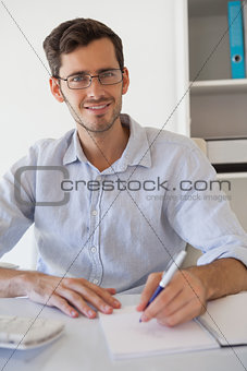 Casual smiling businessman taking notes at his desk